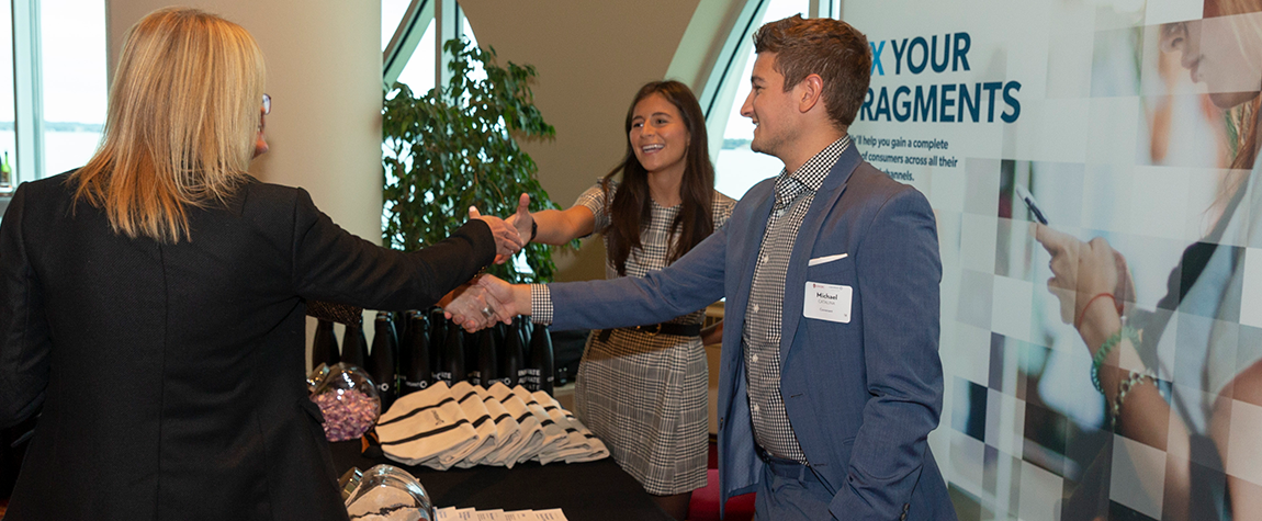 sponsors shaking hands with attendee